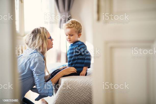 A Young Mother Talking To Her Toddler Son Inside In A Bedroom Stock Photo - Download Image Now