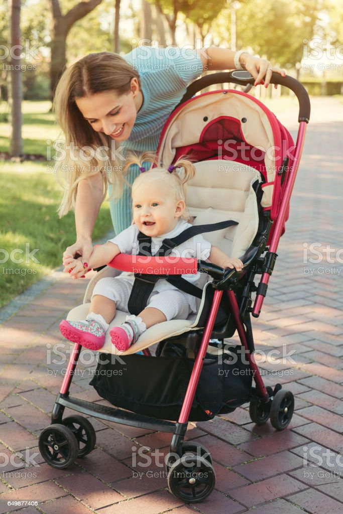 Young mother talking to smiling baby in pink stroller. Parents walking outdoors with child in summer pram. - Photo