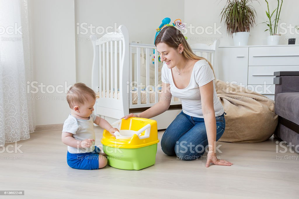 Young mother teaching her baby how to use chamber pot - foto de stock