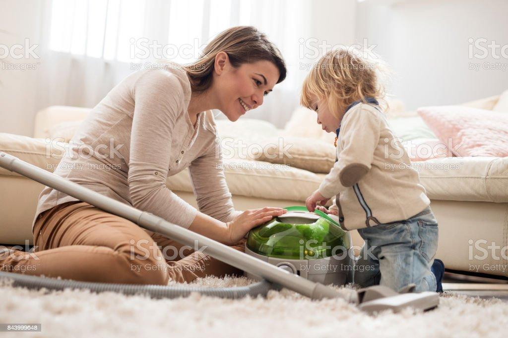 Young mother teaching her small son how to use vacuum cleaner at home. - foto stock