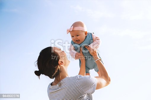 istock Young mother throws up baby in the sky, summer outdoors. 944502276