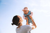 Young mother throws up baby in the sky, summer outdoors. Happy mom and cute smiling baby girl. Positive human emotions, feelings, natural lifestyles. Family background.