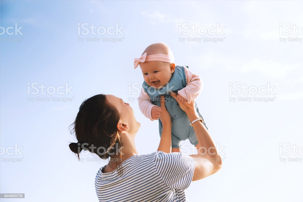 Young mother throws up baby in the sky, summer outdoors. stock photo