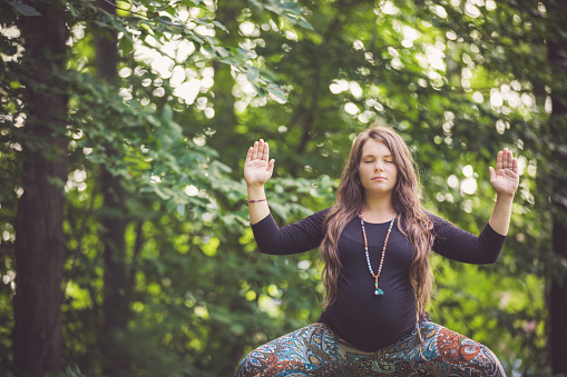 Beautiful young mom to be practicing prenatal yoga and meditation