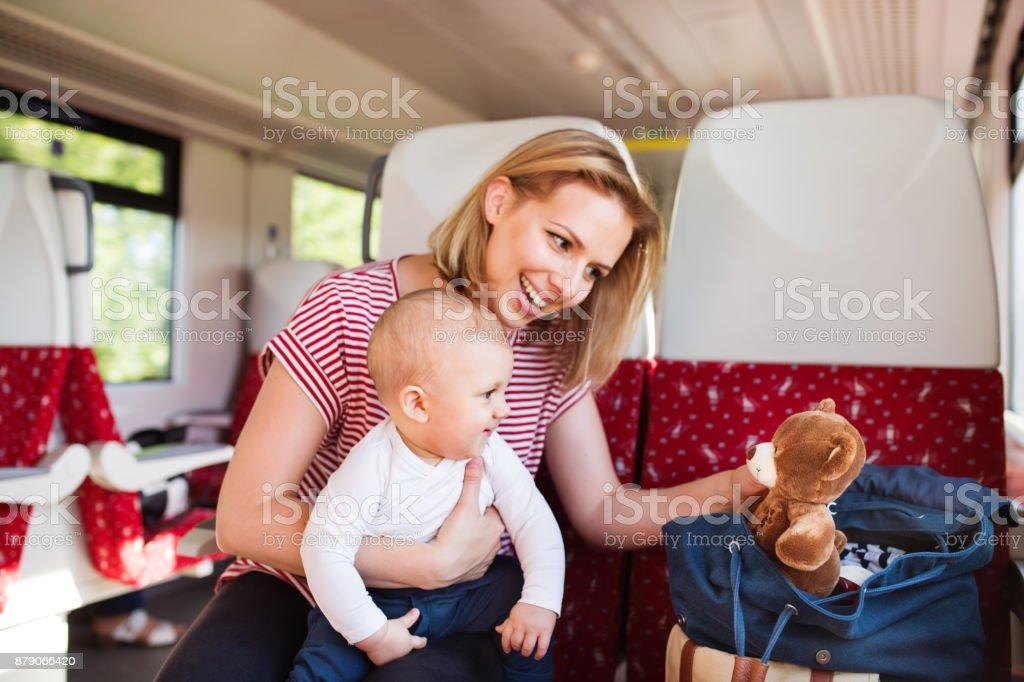 Joven madre con bebé de viaje en tren. - foto de stock