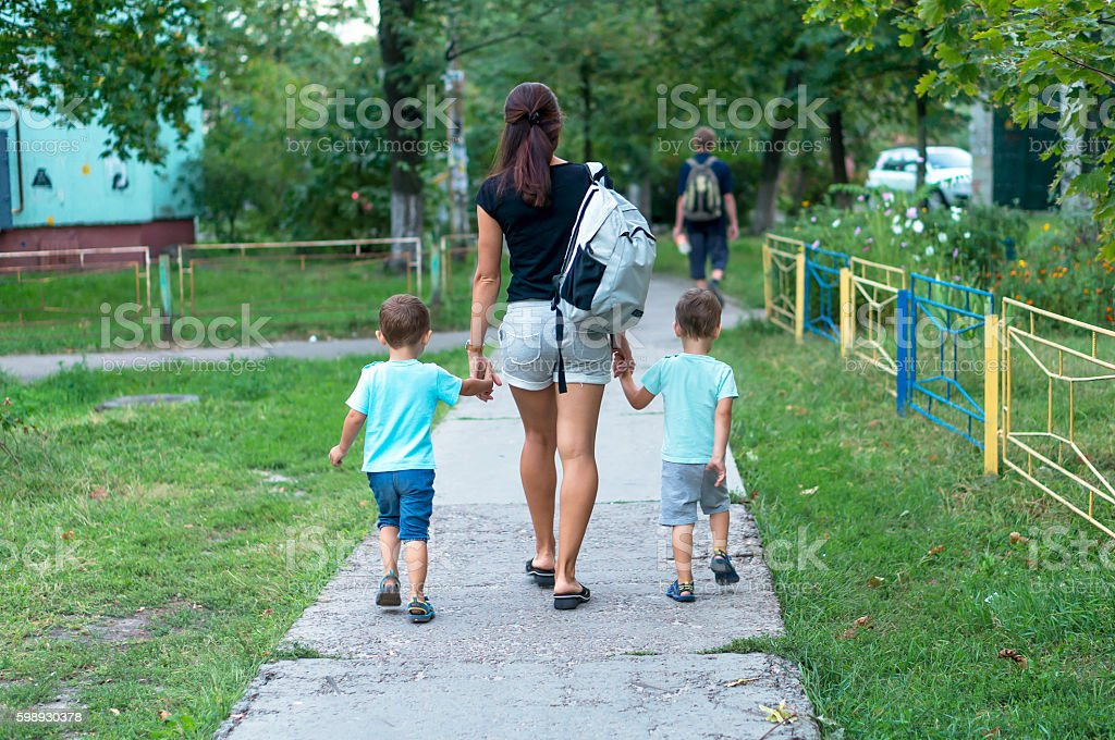 Young mother walking and holding hands two boys stock photo