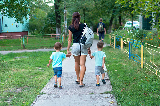 Young mother walking and holding hands two boys - Photo