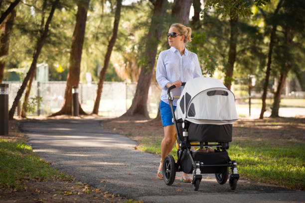 Young mother walking and pushing a stroller in the park. Mother strolling with newborn. Beautiful happy mother with pram outdoors. Summer walks in the sunny day. Girl with carriage. stock photo