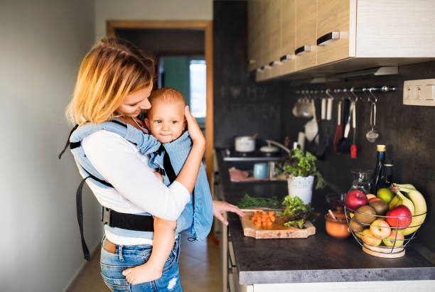 Young mother with a baby boy doing housework. stock photo