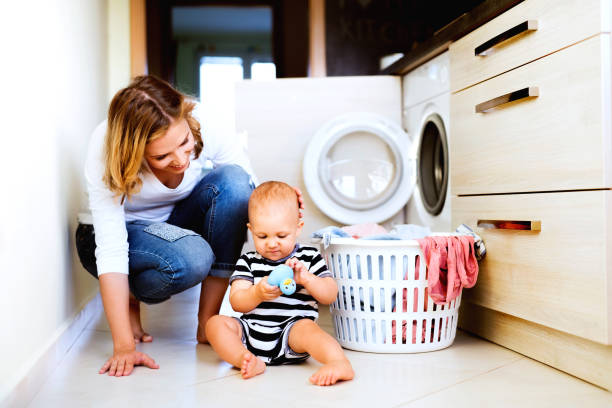 Young mother with a baby boy doing housework. Young mother with a baby son doing housework. Beautiful woman and baby boy doing laundry. kids cleaning up toys stock pictures, royalty-free photos & images