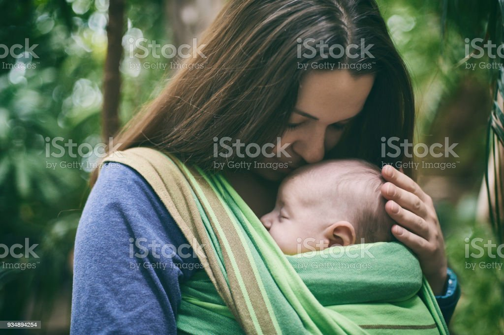 A young mother with a baby in a sling is walking in the jungle stock photo