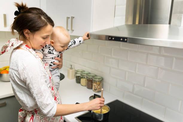 ung mamma med en bebis på händerna lagar maten i en gryta på spisen - superwoman barn bildbanksfoton och bilder