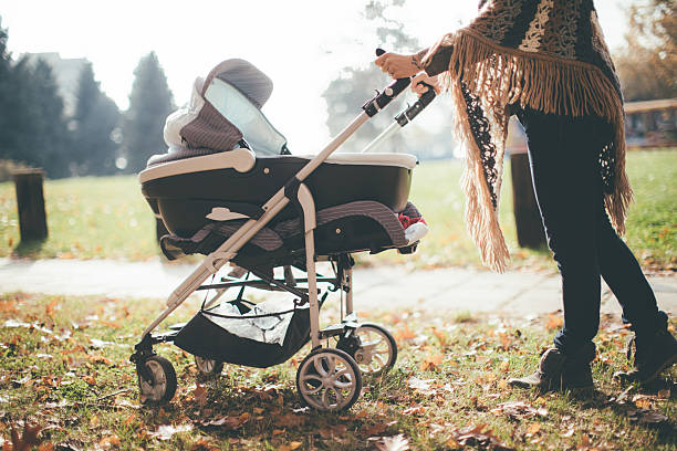 Young mother with a baby stroller stock photo