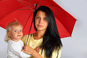 Beautiful young mother with a child with a red umbrella on a light background