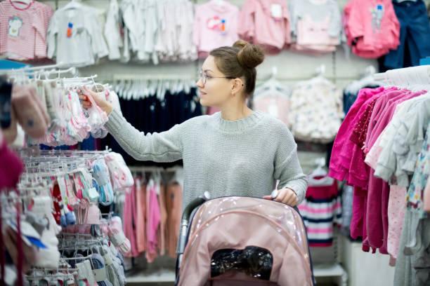 madre joven con un cochecito elige ropa para su hijo - foto de stock