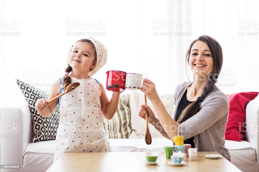 Young mother with a small girl at home, playing. stock photo