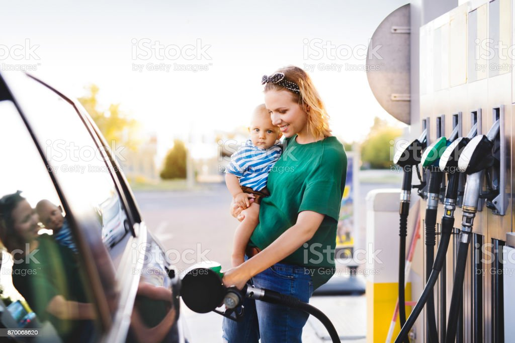 Young mother with baby boy at the petrol station. royalty-free stock photo