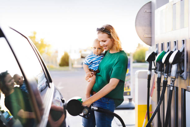 Young mother with baby boy at the petrol station. stock photo