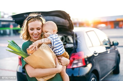 istock Young mother with baby boy in front of a supermarket. 870070926