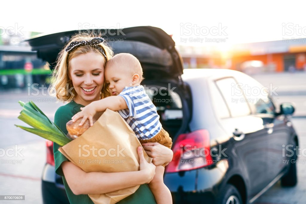 Young mother with baby boy in front of a supermarket. stock photo