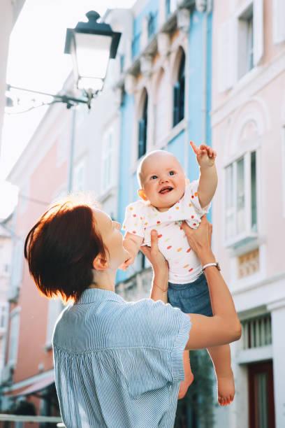 Joven madre con bebé en calles europeas históricas de la vieja ciudad de Piran, Eslovenia, Europa. - foto de stock