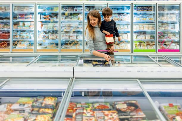 jovem mãe com filho escolhendo produtos em supermercado - comida congelada - fotografias e filmes do acervo