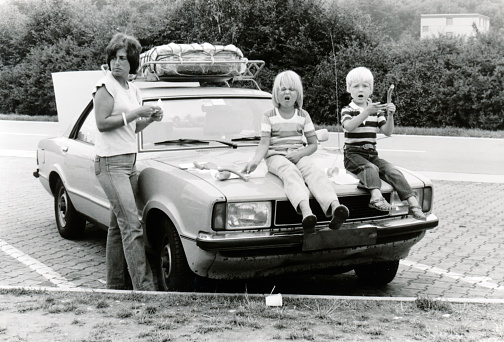 Vintage monochrome 1978 image; young mother with daugter and son sitting on hood of car eathing lunch sausages on a roadtrip holiday in Germany.