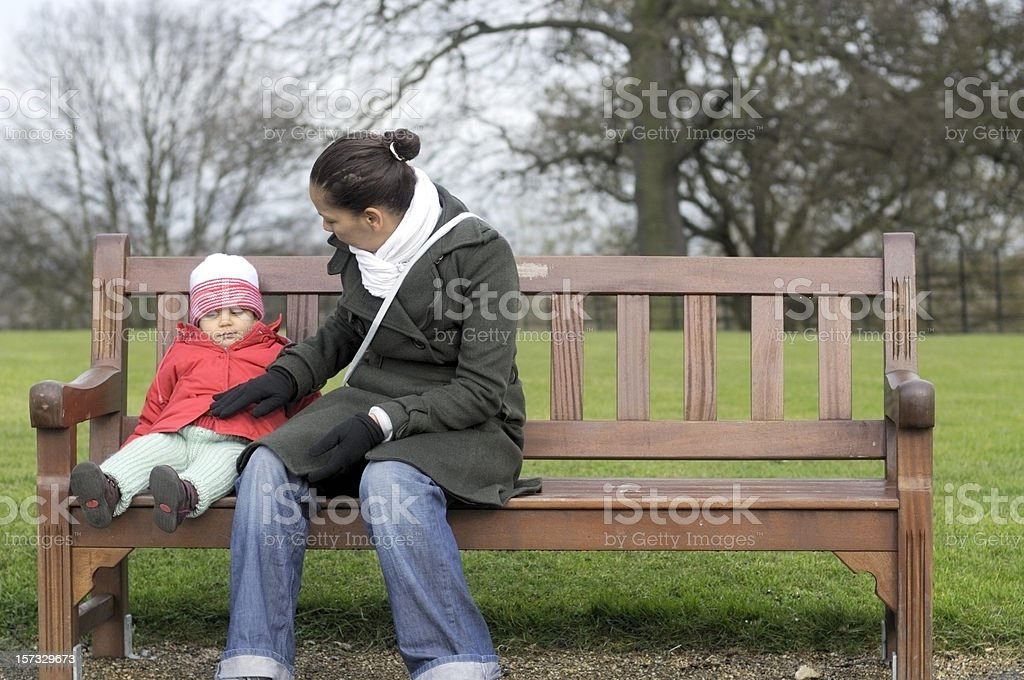 Young Mother With Her Baby Girl Sitting on Bench royalty-free stock photo