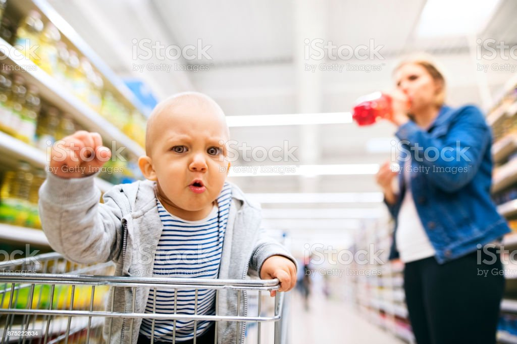 d0e25680896c17 Junge Mutter mit ihrem kleinen Baby-jungen im Supermarkt. Lizenzfreies stock -foto