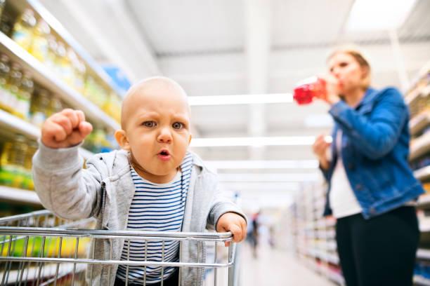 junge mutter mit ihrem kleinen baby-jungen im supermarkt. - angry stock-fotos und bilder