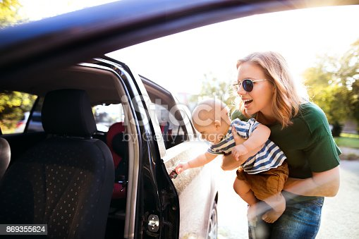 istock Young mother with her little baby boy standing by the car. 869355624