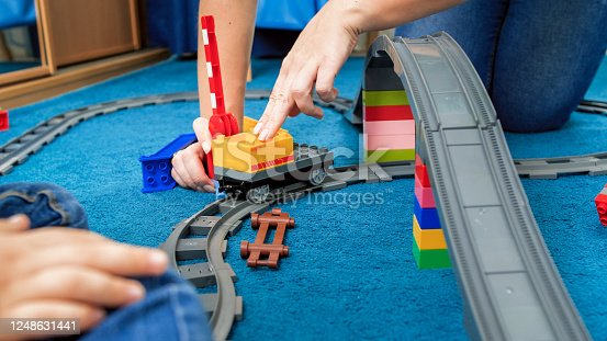 917360086 istock photo Young mother with her little playing a game with trains and railroad on floor 1248631441
