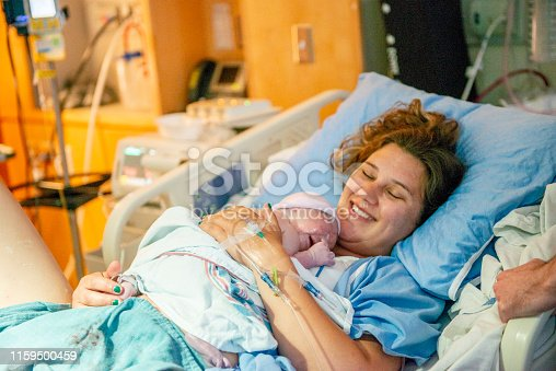 Mother holds her newborn baby in the hospital immediately after giving birth.