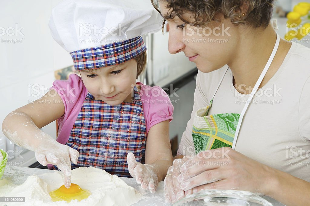 Young mother with little daughter preparing cookies royalty-free stock photo