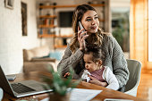 Smiling mother holding small daughter in her lap while talking on the phone at home.