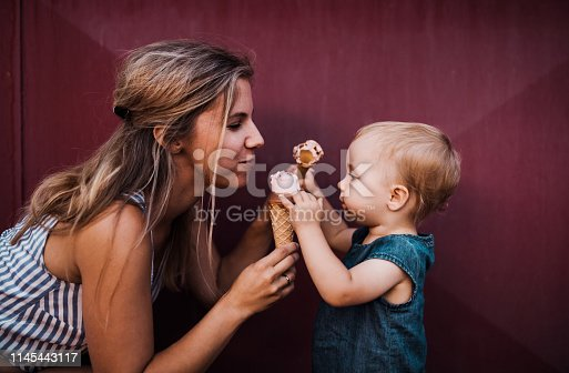 A young mother with small toddler girl outdoors in summer, eating ice cream.