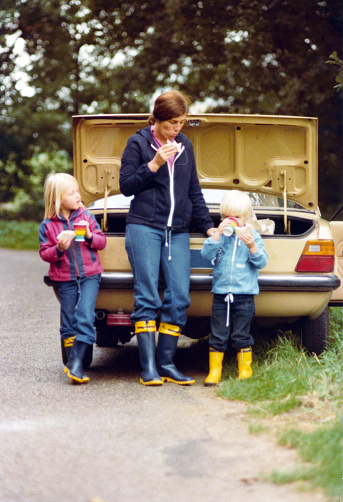 Vintage colorful 1979 image of a young mother with son and daughter standing and eating a sandwich in nature, in front of a seventies car with open car trunk.