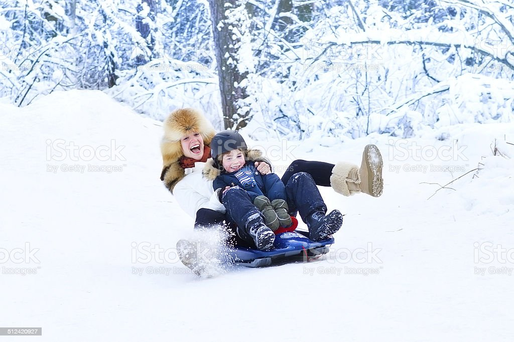 Young mother with son on sleigh ride in snowy park stock photo