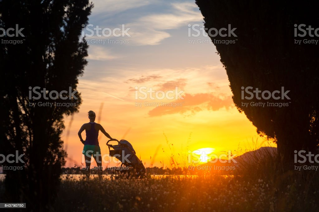 Young mother with stroller enjoying motherhood at sunset landscape royalty-free stock photo