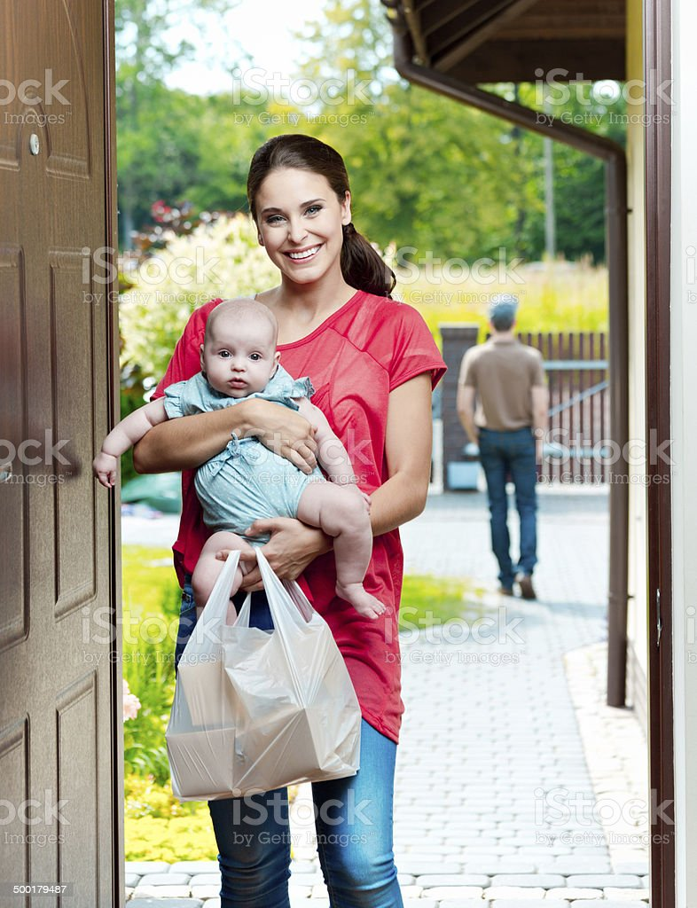 Young mother with take away food Young mother standing at the door of the house, holding his baby and take away food with delivery man in the background. Adult Stock Photo