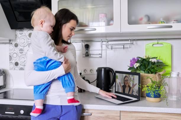 Kollarında yeni yürümeye başlayan genç anne psikologla internette konuşuyor stok fotoğrafı