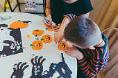 istock young mother with toddler son making craft pumpkins for halloween holiday 1264059077