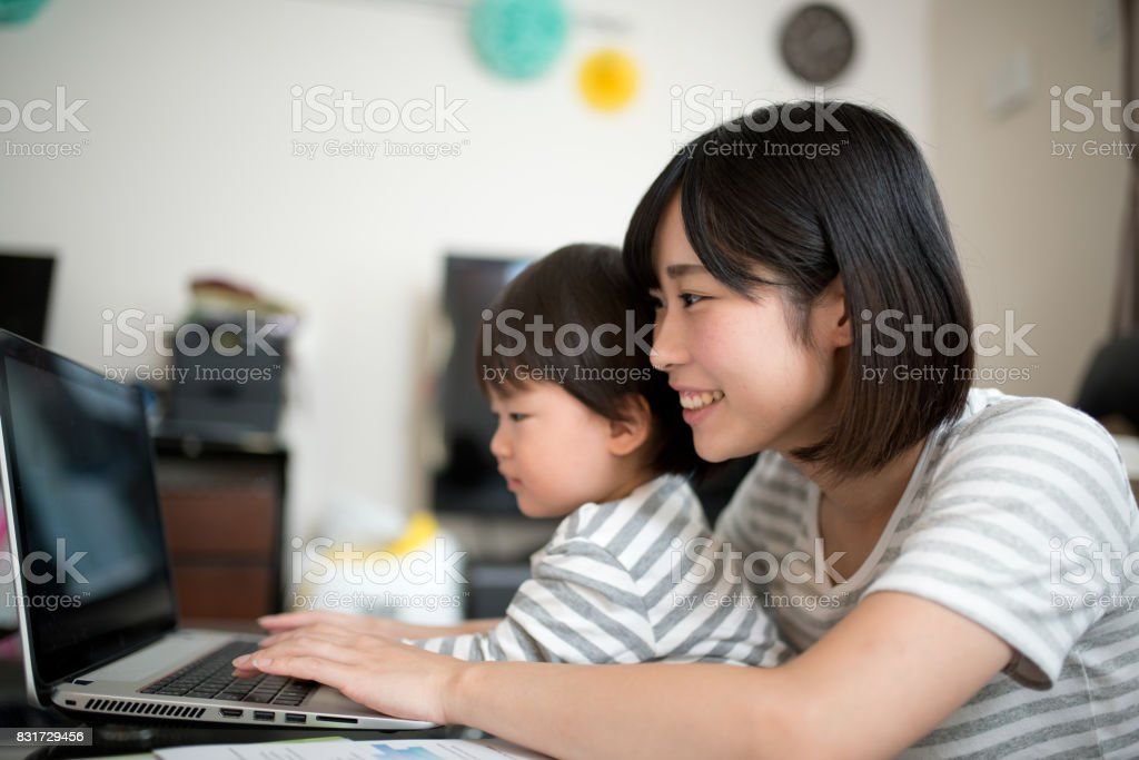 young mother working in house with her child stock photo