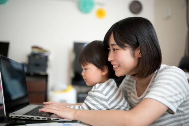 若い母親は彼女の子供と家の中の作業 ストックフォト