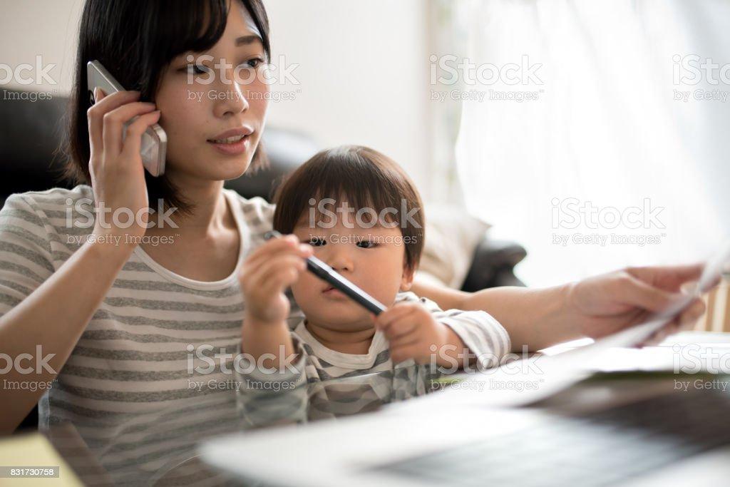 若い母親は彼女の子供と家の中の作業 ロイヤリティフリーストックフォト