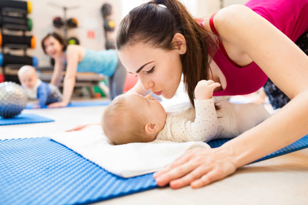 Young mothers exercising with their babies in modern gym. Close up of mother kissing baby. stock photo