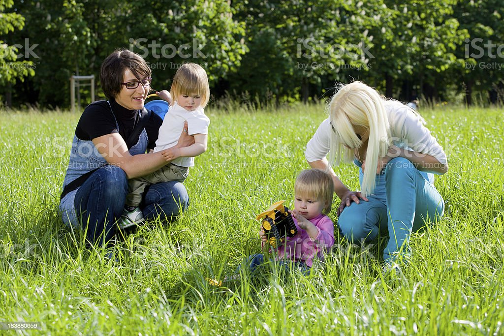 Young mothers in park playing with their babies stock photo
