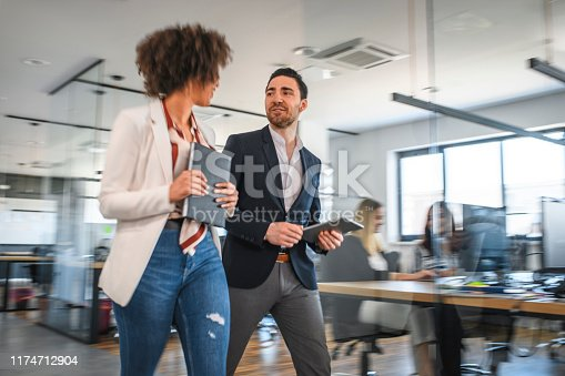 1163429625istockphoto Young Motivated Business Colleagues Walking and Talking 1174712904