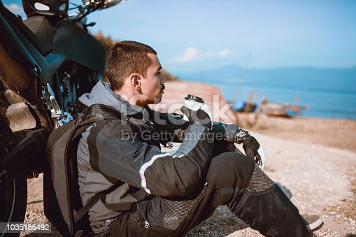istock Young Motorcyclist Drinks Coffee to go and Enjoys the View on his Ride Brake 1035185492