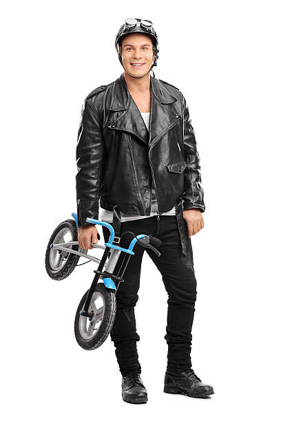 Young motorcyclist holding a small bicycle stock photo